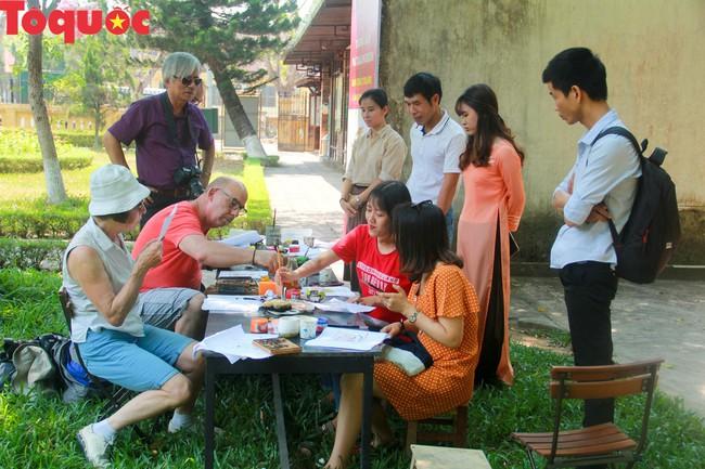 Du khách quốc tế thích thú trải nghiệm làm tranh làng Sình tại Huế - Ảnh 7.